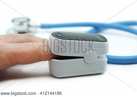 Pulse Oximeter And Stethoscope Isolated On White Background. Pulse Oximeter Used To Measure Pulse Ra