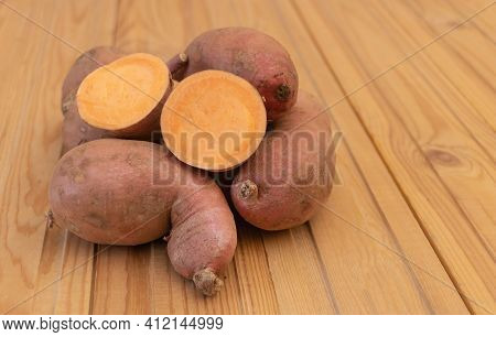 Sweet Potatoes On Wooden Background - Cut In Half - Benefits Of Sweet Potatoes Concept. Selective Fo