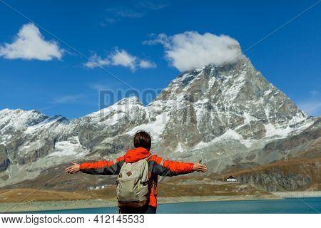 Rear View At Happy Free Woman Is In Front Of The Matterhorn Alpine. Joyful Female Model Breathing Fr