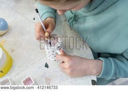 A Young Woman In Casual Clothes Paint A Pink Heart On The Back Of A Ceramic Cup In A Ceramic Worksho