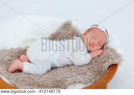 Newborn Baby In White Knitted Suit Sleep In Wooden Basket.