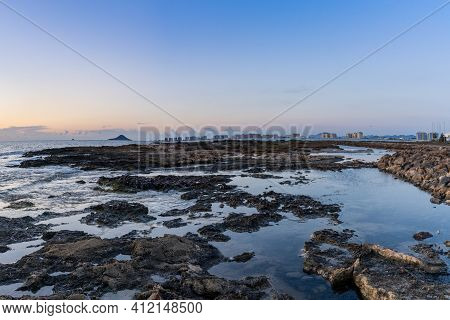Many Rocky Tidal Pools With The Hotels Of La Manga Del Mar Menor In The Background