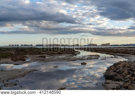 Scenic Reflections Of Sky In Rocky Tidal Pools With The Hotels Of La Manga Del Mar Menor In The Back