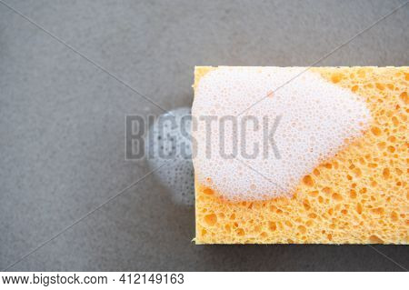 Close Up Of Yellow Scouring Sponge On The Kitchen Counter Top With Soap Scum.concept Of Cleanliness