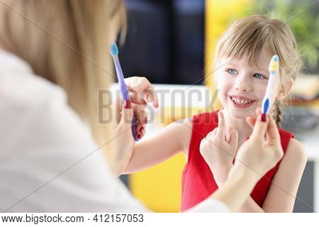 Little Girl Choosing Toothbrush From Doctors Hands In Clinic. Childrens Dentistry Concept