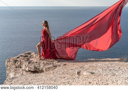 A Girl With Loose Hair In A Red Dress Stands On A Rock Rock Above The Sea. In The Background, The Se