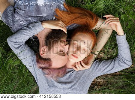 Couple Relationship. Beautiful Couple, Seated Down On A Green Grass, Seated Down With Turned Heads W