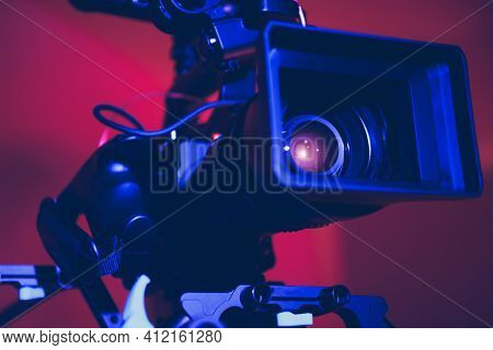Modern Digital Cinema Camera With Moto Zoom Telephoto Lens Attached In Blue And Red Film Stage Illum