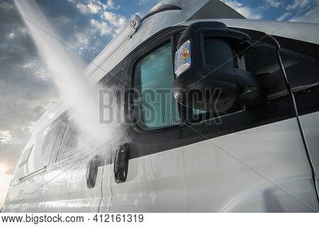 Summer Season Preparation. Pressure Washing Rv Camper Van Close Up. Recreational Vehicle Maintenance