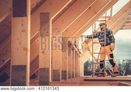 Caucasian Contractor In Hard Hat And His Residential Building Wooden Skeleton Construction Job. Hous