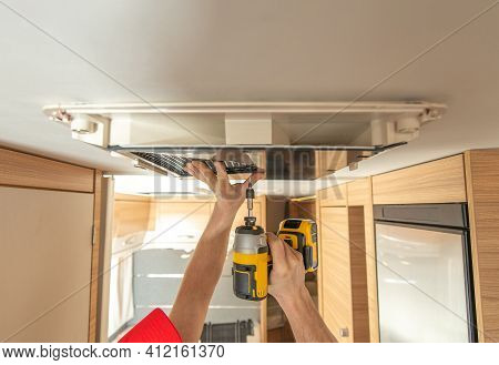 Rv Recreational Vehicles Caucasian Technician Worker In His 40s Replacing Air Conditioner Unit Insid