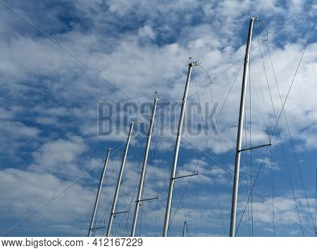 Row Of Metal Yacht Masts In Front Of Blue Sky And White Clouds