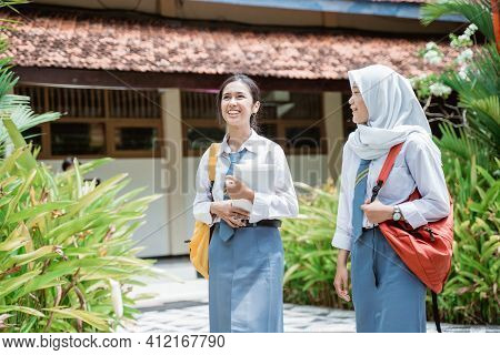 Two Smiling High School Girls Wearing School Bags And Carrying Books Walking Together