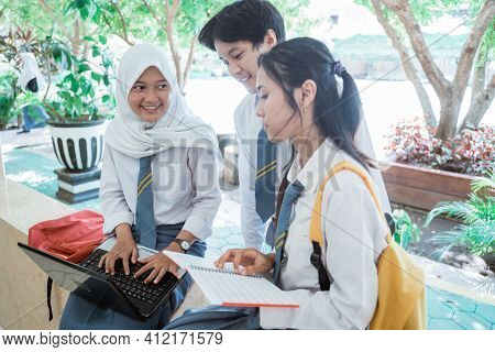 Group Of High School Students Standing With A Laptop Computer, Carrying Books, And Wearing A Bag