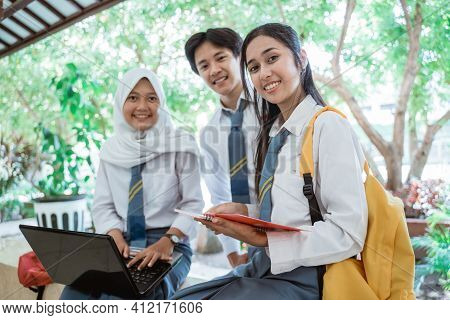 Three High School Students Smiling At The Camera While Standing On A Laptop Computer, Carrying Books