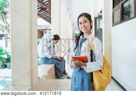 A Smiling Student Wearing An Indonesian High School Uniform Carrying Book And A School Bag