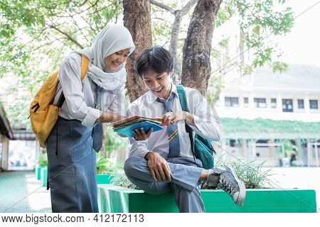 A Handsome Boy And Veiled Girl In Indonesian High School Uniform Reading Book Together With Copy Spa