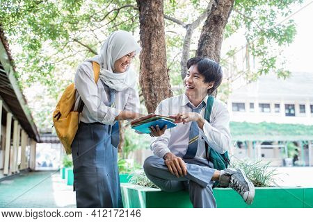 A Smiling Boy And Veiled Girl In Indonesian High School Uniform Chat Under The Tree While Reading A