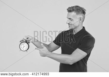 Look At Clock. Handsome Man Point Finger At Alarm Clock. Check Current Time. Countdown And Deadline.