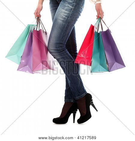 Shopping bags near legs in jeans and high heels over white background