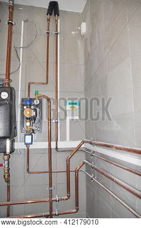 Heating System With Copper Pipes, Copper Tubing, Heat Pump, And Control Panel In A Boiler Room.