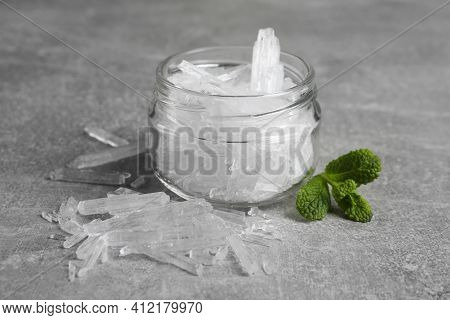 Menthol Crystals And Fresh Mint Leaves On Grey Background
