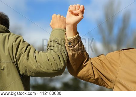 People Greeting Each Other By Bumping Elbows Instead Of Handshake Outdoors, Closeup