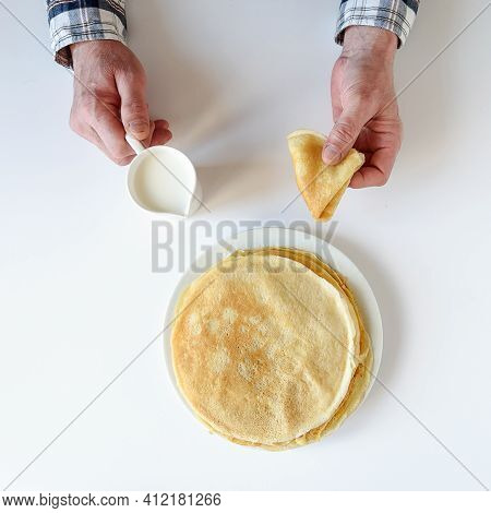 Men's Hands Hold Milk And A Pancake. There Are A Lot Of Pancakes On A White Plate. Thin Pancakes Wit