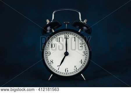 The Time Is Seven O'clock In The Morning. Time - 07-00. Retro Clock. Dark Background. Lifting Concep