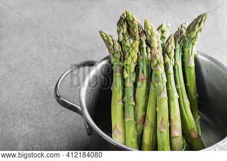 Cooking Asparagus In A Pot. Fresh Asparagus Boiled On Water For Cooking Meal. Healthy Food Concept.