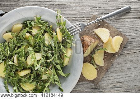 Healthy Dandelion Salad With Potatoes On Wooden Background Close Up