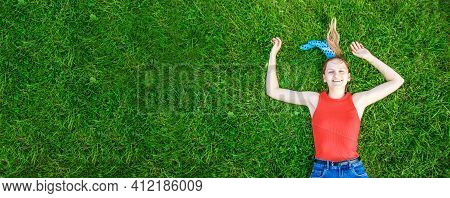 Relaxation And Meditation Concept. Young Blonde Girl Lies On Green Grass Looks At The Camera Outside