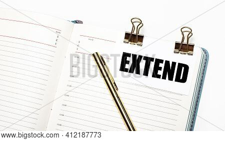 On A Light Background, An Open Notebook, A Sheet Of Paper With Gold Clips And The Text Extend And A