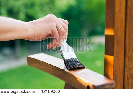 Female Hand Holding A Brush Applying Varnish Paint On A Wooden Garden Chair - Painting And Caring Fo