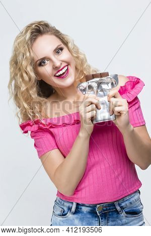 Portrait Of Positive Smiling Caucasian Blond Girl With Unwrapped Bar Of Chocolate Posing On White. V