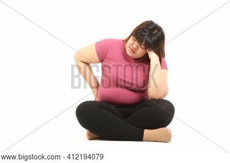 Fat Asian Woman Wearing Gym Clothes Sit Stressed On A White Background. The Concept Of Losing Weight
