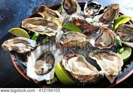 Fresh Oysters With Lime On A Round Plate. Oyster Season. Macro-seafood Dish. Oyster On Half Shell.tw