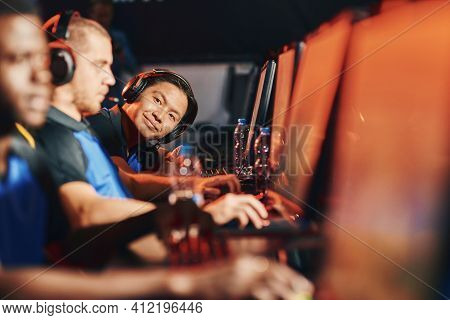 Male Cybersport Gamer Wearing Headphones Looking At Camera And Smiling While Sitting In A Row With O
