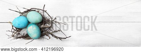 Easter Background With Easter Eggs Nest And Twigs On A Painted Wooden Background. Top View With Copy