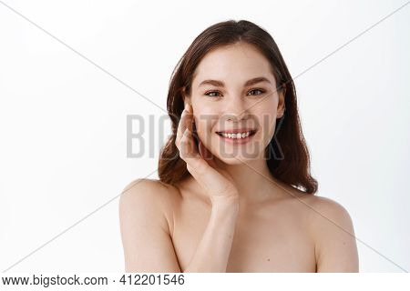 Skin Care Beauty. Feminine Model With Hydrated Healthy Skin, Glowing Face, Touching Cheek And Smilin