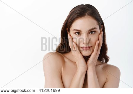 Young Woman Touching Moisturized Clean And Hydrated Facial Skin, Holding Hands On Soft Cheeks, Gazin