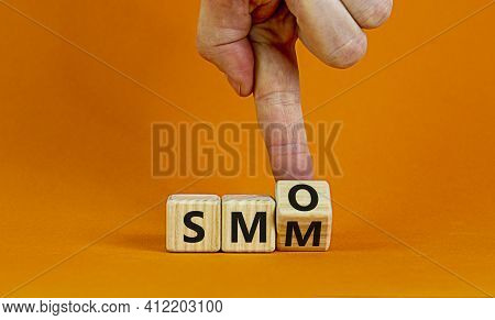 Smm Vs Smo Symbol. Businessman Turns A Cube And Changes Words 'smm, Social Media Marketing' To 'smo,