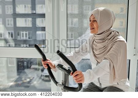 Beautiful Sporty Arab Woman Cycling A Bike At Home. Cardio Training, Exercising Legs, Cardio Workout