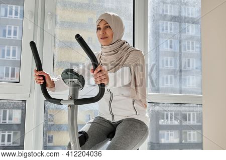Attractive Muslim Woman Exercising On A Stationary Bike At Home On A Beautiful Sunny Day. Cardio Wor