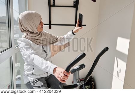 Attractive Muslim Woman Doing Selfie Exercising On A Stationary Bike At Home On A Beautiful Sunny Da