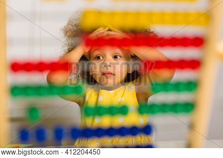 A Black Girl In A Yellow Dress Is Puzzled By An Example Of Arithmetic That She Must Count On The Aba