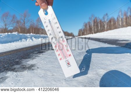 The Thermometer Shows A Negative Temperature In Cold Weather Against The Background Of An Icy Road O