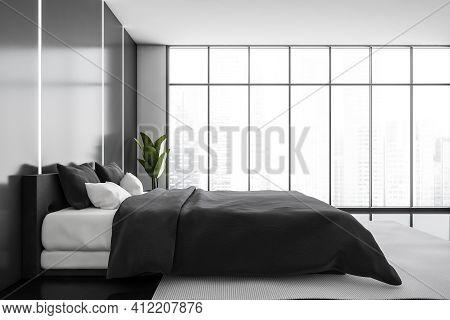 Dark Bedroom Interior With Furniture On Black Floor, Plant In The Corner, Panoramic Windows. Backlig