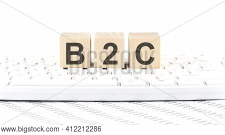 B2c -word Wooden Block On The Keyboard Background Witn Chart