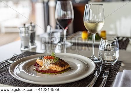 Gourmet Dish In Elegant Modern Restaurant. Delicious Portion Of Fresh Salmon Fillet, White Wine With